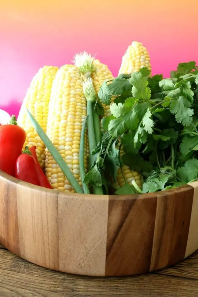 A wooden bowl filled with fresh corn, red jalapenos, green onions and cilantro.