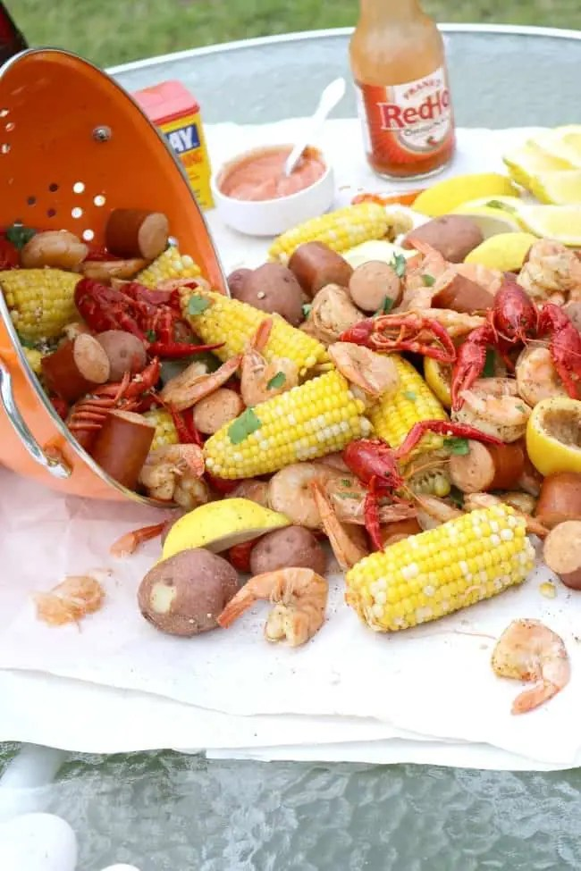 A side view of a lowcountry crawfish boil laid out on a picnic table with fresh corn, keilbasa, andouille sausage, shrimp, and crawfish.