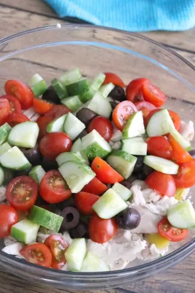 This Easy Greek Chicken Salad is loaded with fresh Mediterranean ingredients like fresh lemon juice, olives, tomatoes, cucumber, Greek yogurt, and feta cheese. This make-ahead dish is perfect for summer entertaining. cucumber, and feta cheese.