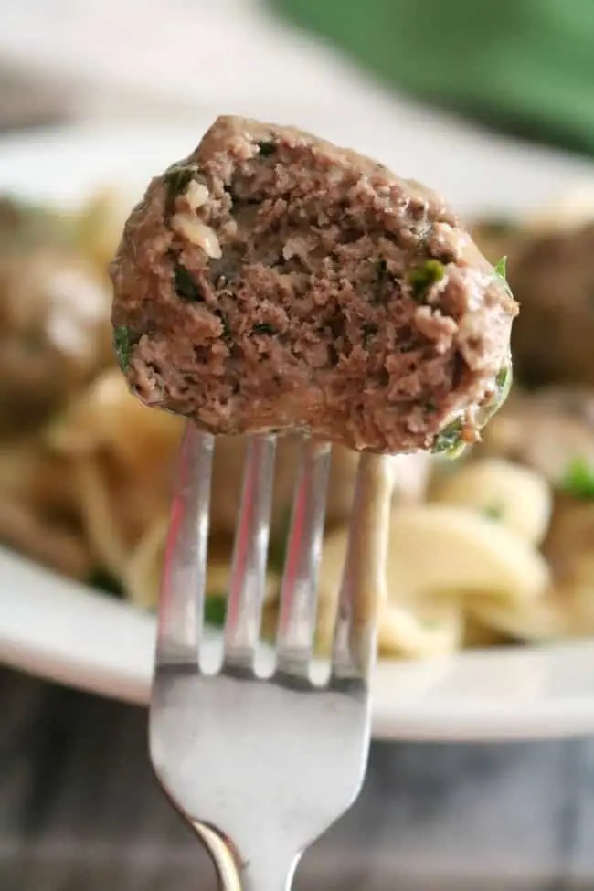 A meatball on a fork with a bite taken out of it. The interior of the meatball reveals herbs and spices.