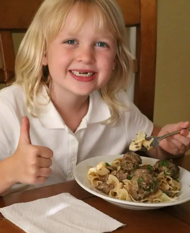 A smiling child eating a plate of meatballs stroganoff giving the viewer a thumbs up.