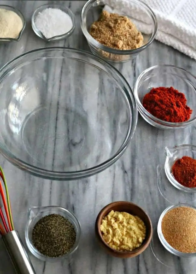 Dry rub ingredients surrounding an emply glass bowl.