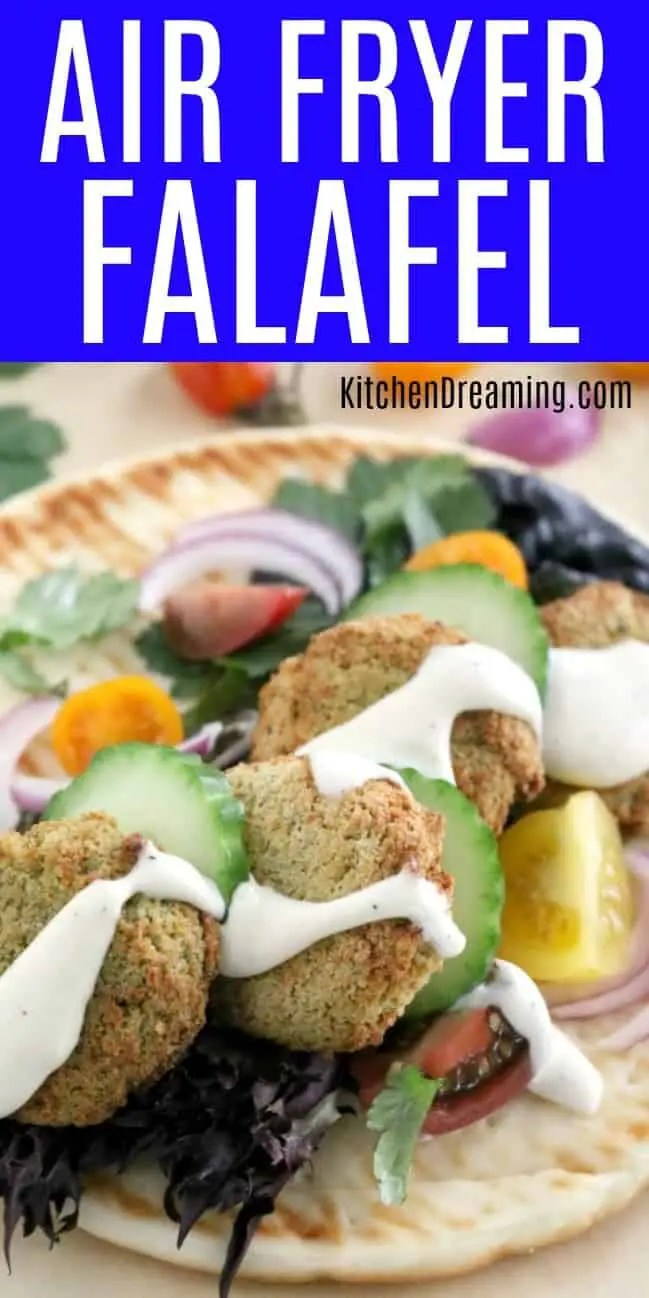 a pinnabble image of Air Fryer Falafel on pita bread topped with cucumbers, red onions, tomatoes, and tatziki sauce.