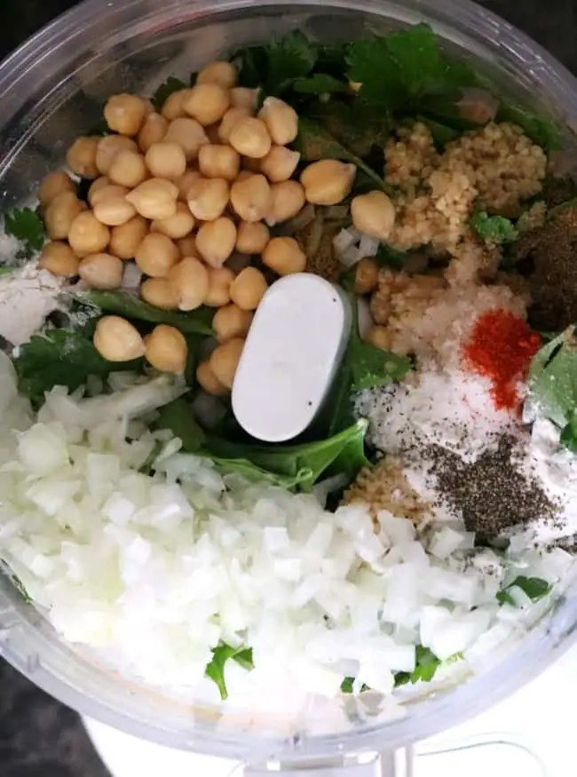 an overhead shot of the ingredients for air fryer falafel in a food processor: chick peas, minced garlicm salt, onions, black pepper, and parsley getting ready to be ground to for the raw falafel mix.