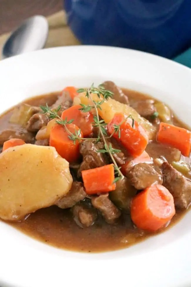 A close-up image of a bowl of Irish Beef & Guinness Stew topped with a sprig of lemon thyme.