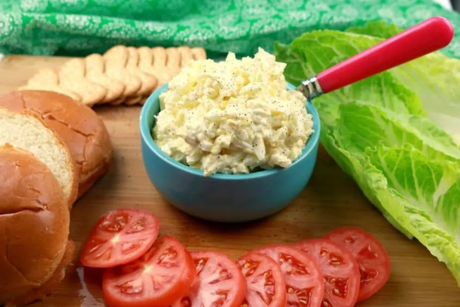 a horizontal image of egg salad on a wooden board. the bowl is surrounded by lettuce, tomatoes, brioche rolls, and crackers