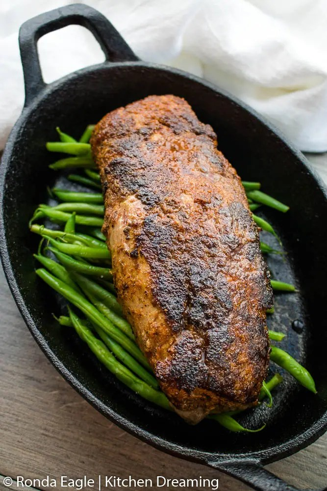 An oblong cast iron skillet filled with roasted green beans and a whole pork tenderloin.