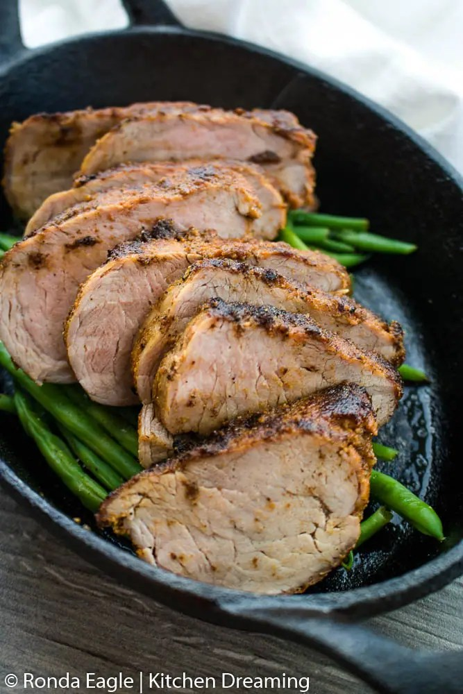 An oblong cast iron skillet filled with roasted green beans and sliced pork tenderloin.