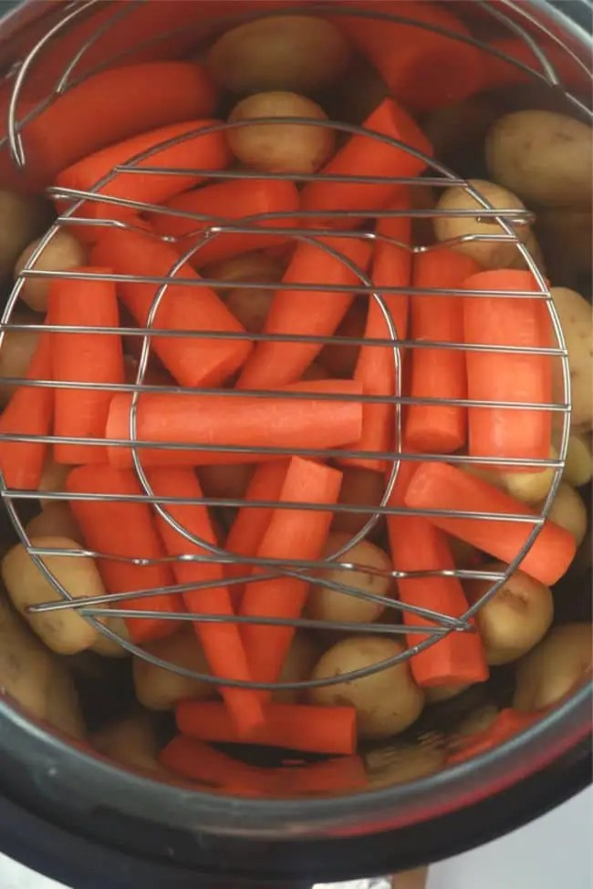 Baby potatoes and carrots loaded into the Instant Pot. A steam rack has been placed on top of the vegetables to support the meatloaf packet.