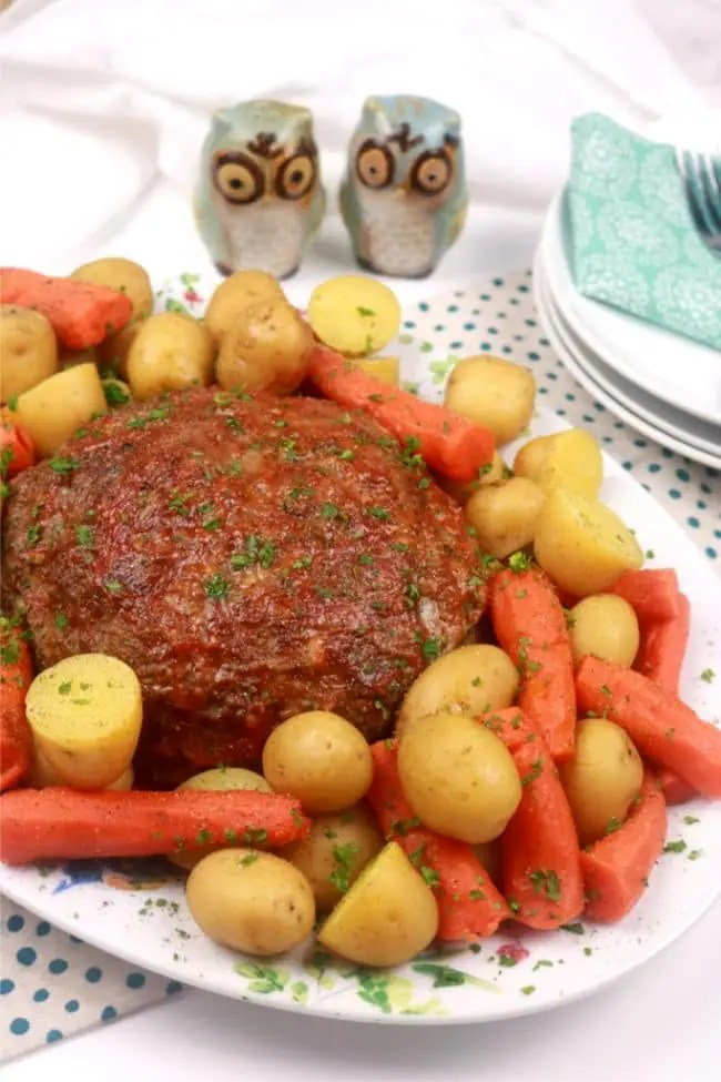 A platter of instant Pot Pressure Cooker Meatloaf dinner on a white table with dishes and blue polka dotted napkins.