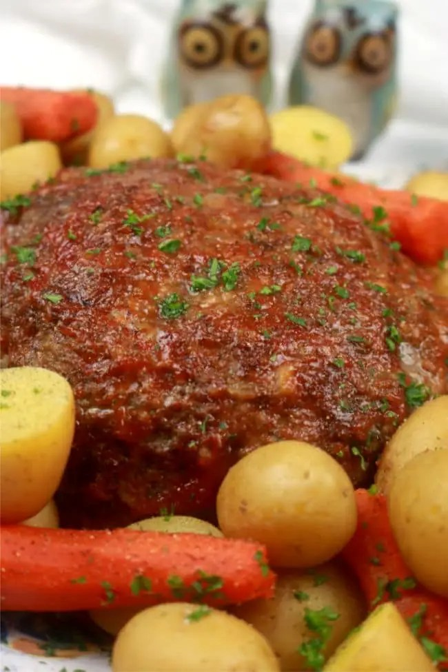 An up close photo of instant pot meatloaf on a platter with steamed potatoes and carrots.