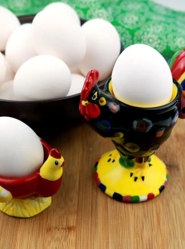 A bowl of whole raw eggs in their shells and two egg holder cups aslo holding eggs