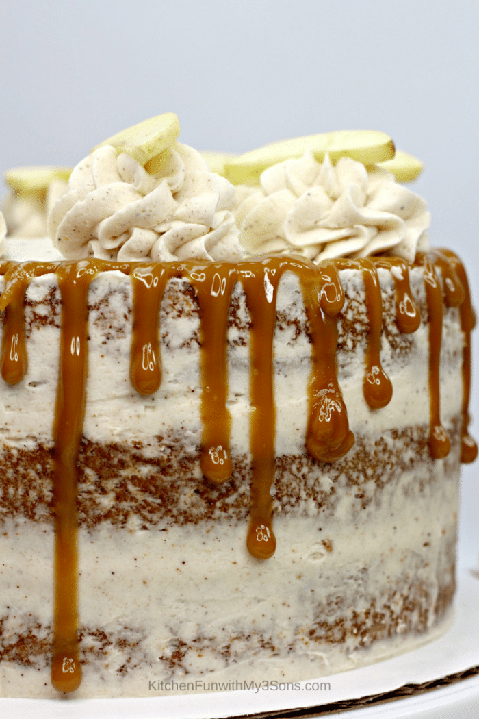 An up close picture of an apple spice cake with frosting and caramel drizzle