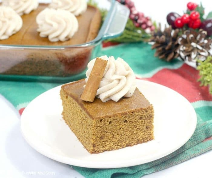 A slice of gingerbread cake on a white plate with holiday decor in the background