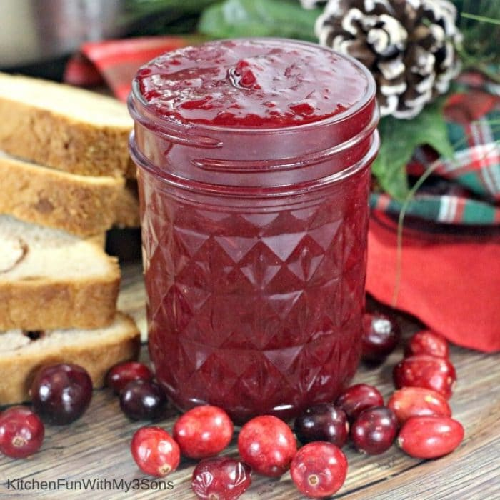 Small mason jar filled with Instant Pot Cranberry Butter in front of holiday decorations
