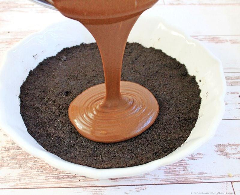 pouring chocolate fudge pie filling into drust