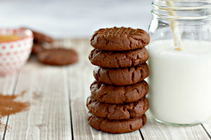 Chocolate Peanut Butter Cookies stacked next to a jar of milk