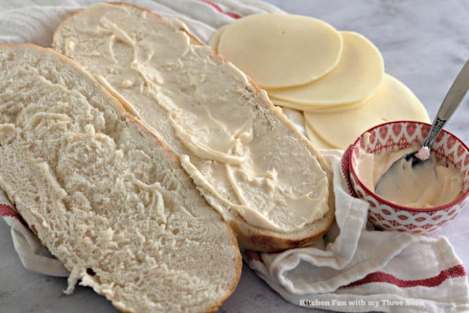 Coating fresh bread with mayonnaise