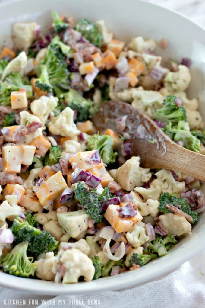 Tossing Low Carb Broccoli Salad in a large mixing bowl with a wooden spoon