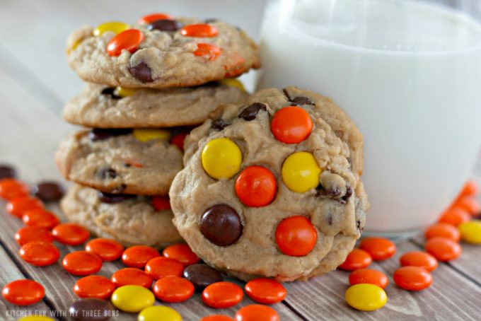 Reese's Pieces Peanut Butter Cookies stacked next to a glass of milk