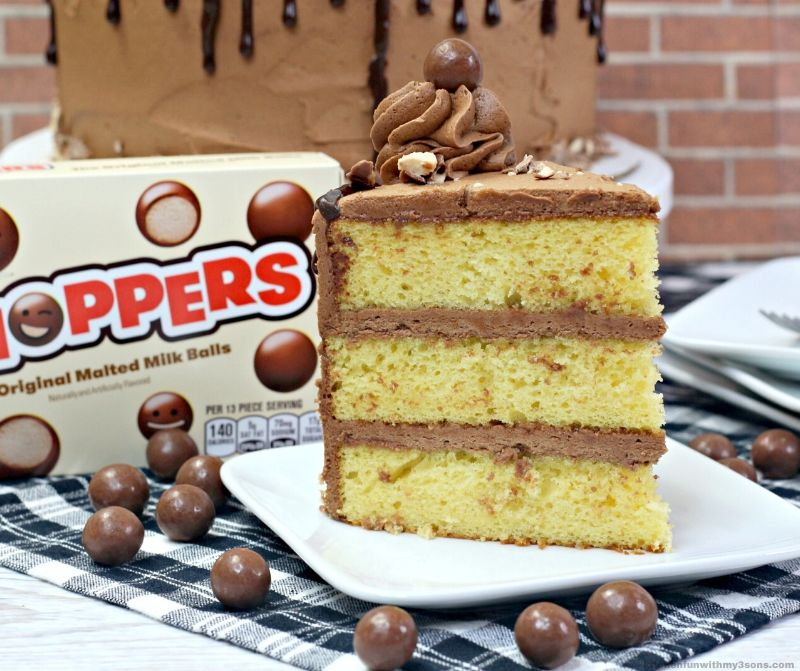 butter cake with chocolate frosting and whoppers on a white plate