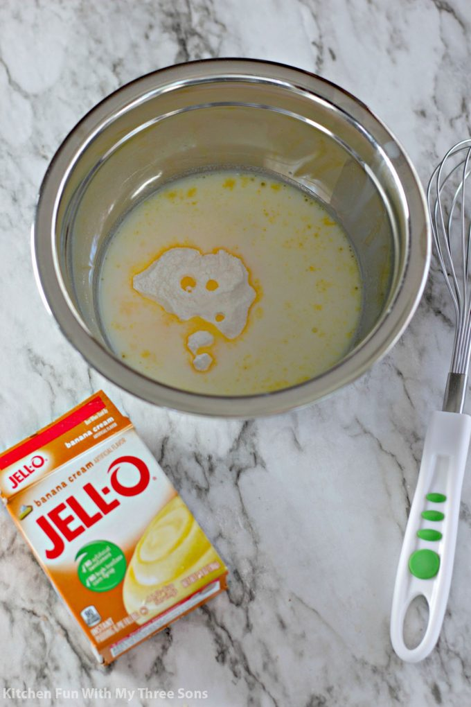 whisking together banana flavored Jello pudding with milk in a stainless steed bowl