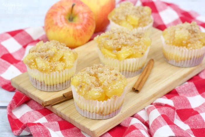 Apple Pie Cheesecake minis are a delicious combo of flaky apple pie and creamy cheesecake. This triple layered treat starts with a graham cracker crust and ends with a homemade crumble topping.