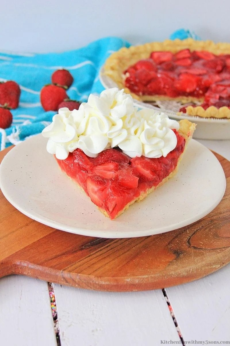 strawberry pie with whipped cream on a white plate