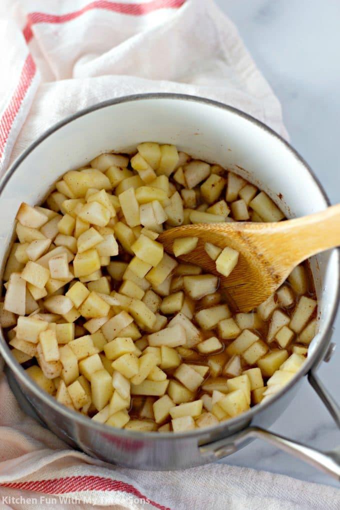 stirring apple chunks into cinnamon, sugar, and water in a saucepan