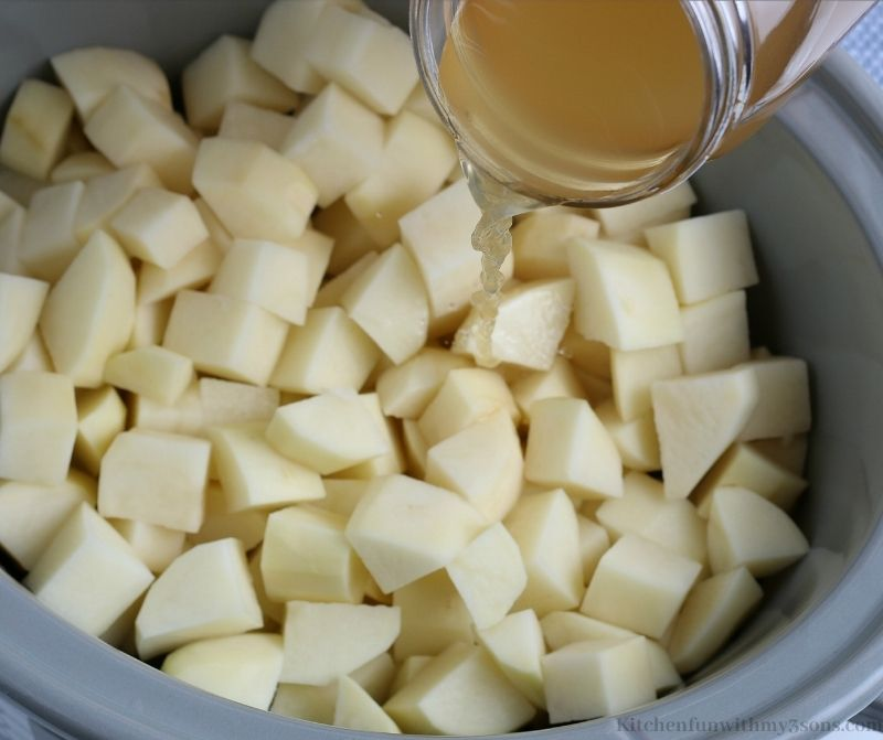 Broth being added over your potatoes in the crock pot.