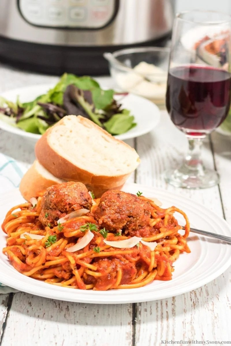 Homemade Spaghetti and Meatballs Recipe with a side salad and wine.
