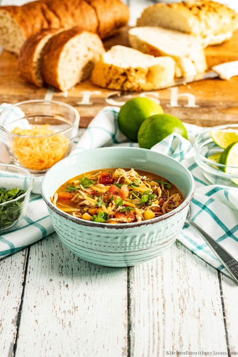 Instant Pot Chili Lime Chicken Soup Recipe with a loaf of bread sliced behind it.