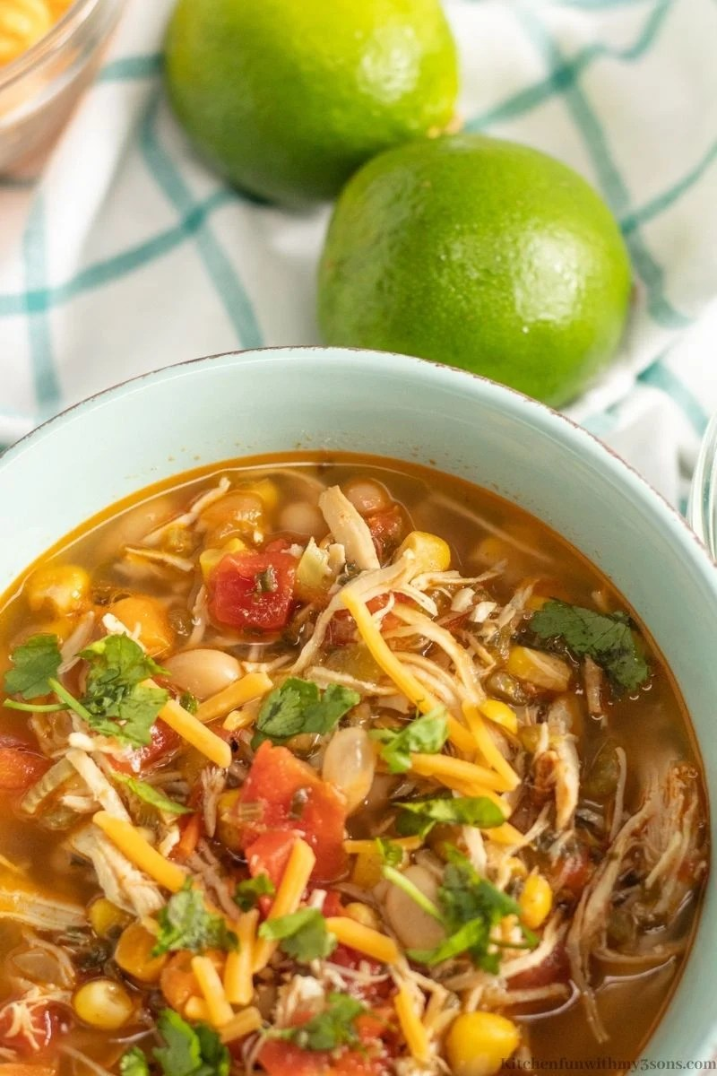 Instant Pot Chili Lime Chicken Soup Recipe with two lemons next to the serving bowl.