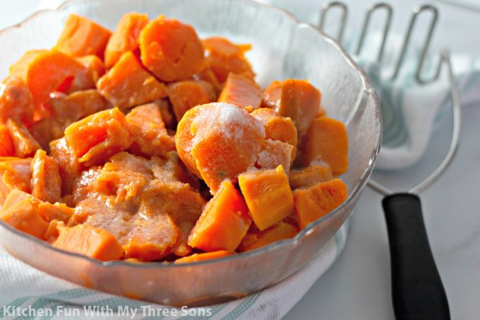 boiled sweet potatoes in a bowl with a potato masher