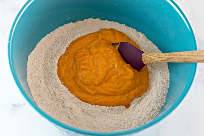 mixing together wet ingredients with the dry into a teal bowl