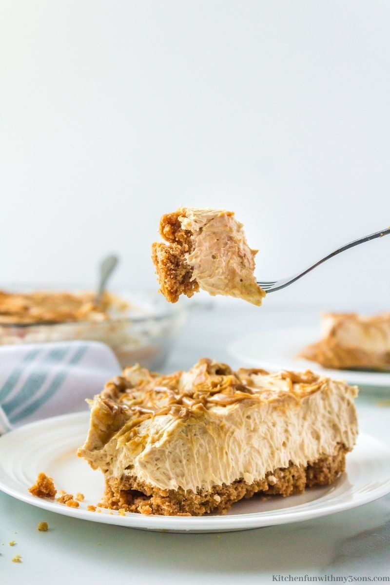 A fork taking a bite out of the slice of Creamy Peanut Butter Pie.