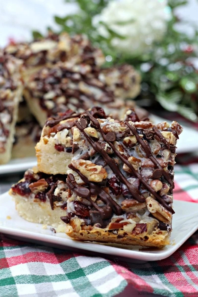 Dark Chocolate Cranberry Magic Bars with leafed decorations in the back.