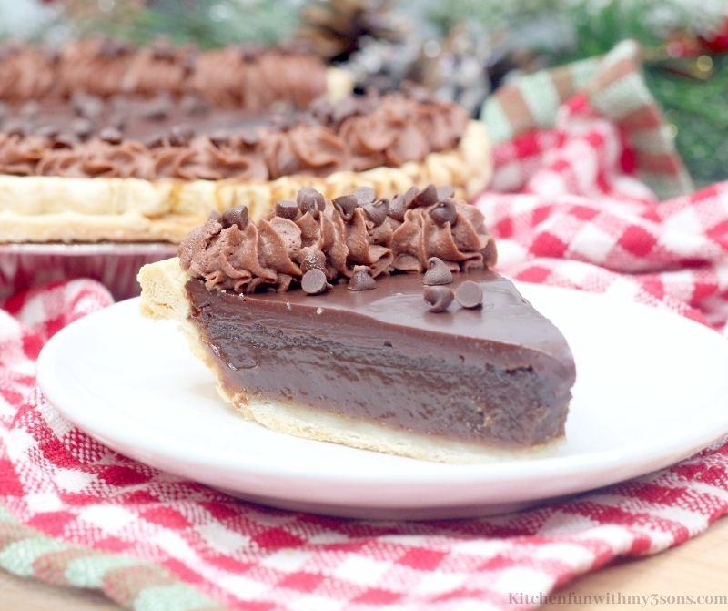 Decadent Chocolate Buttermilk Pie slice with the rest of the pie behind it.