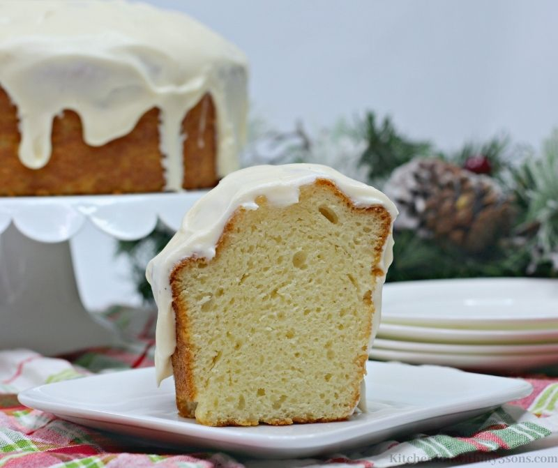 A slice of the Eggnog Cake with the rest of the cake behind it.