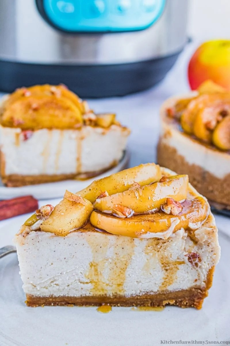 Instant Pot Apple Cinnamon Cheesecake with more slices on serving plates behind it.