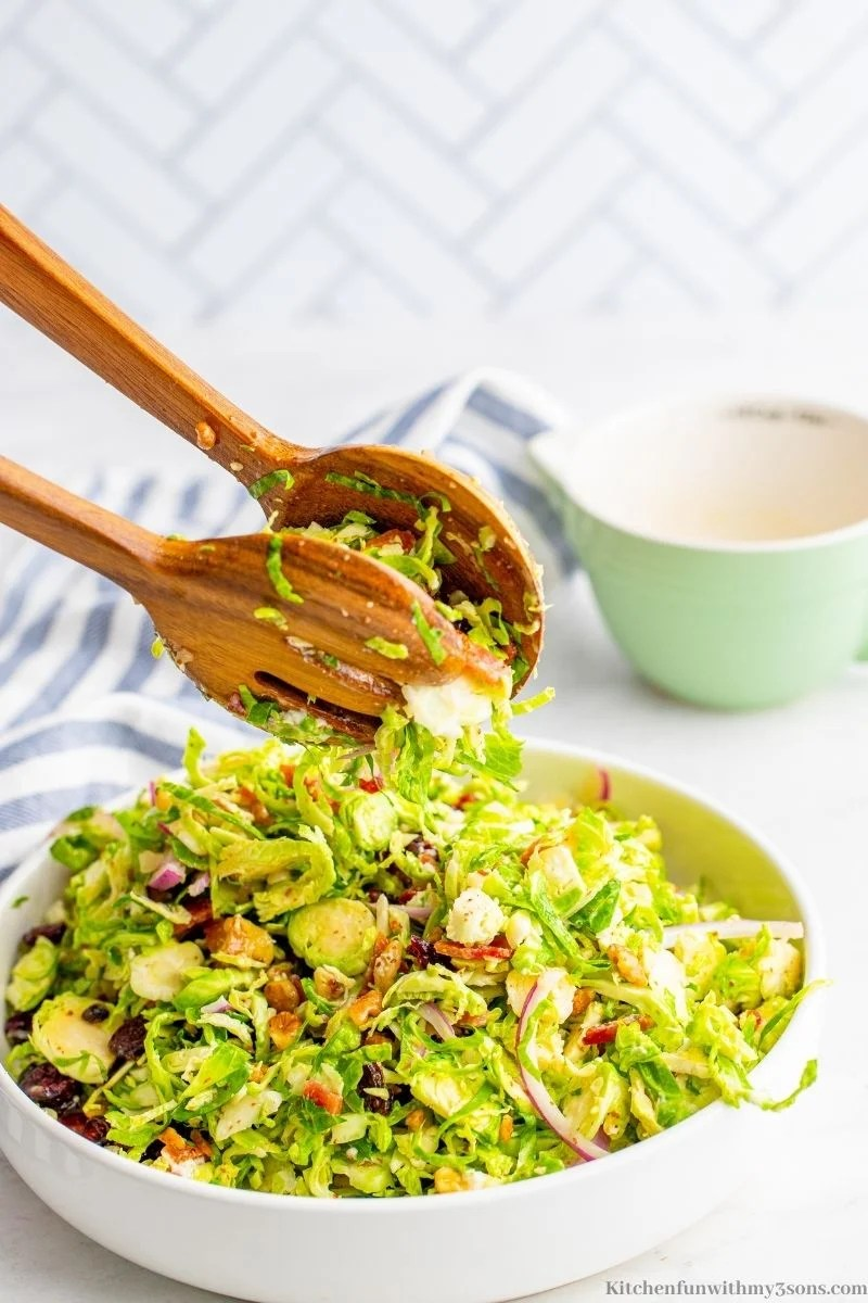 Adding the vinaigrette to the salad and tossing it.