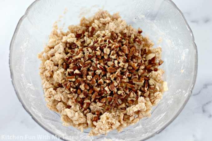 pecans, butter, flour, cinnamon, and brown sugar mixed together in a clear bowl