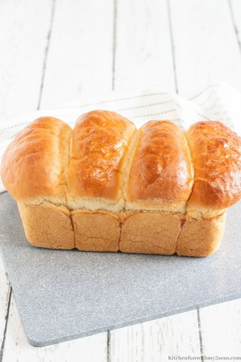 The baked milk bread out of the pan and cooling on a gray slate.