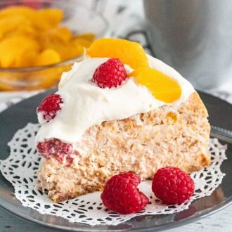 A slice of cheesecake surround by raspberries and peaches on a gray plate and white doily.