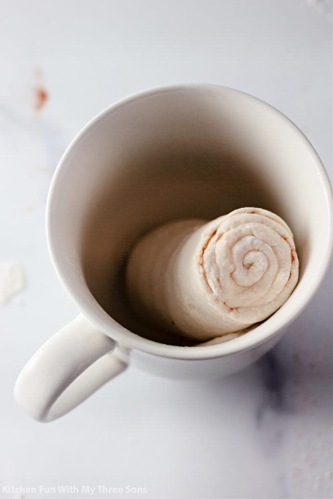 placing the rolled dough into a coffee mug