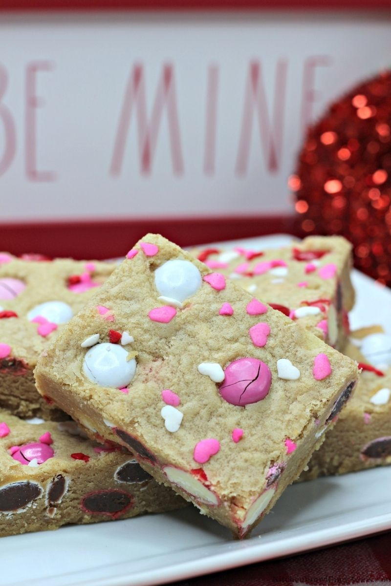 Valentine's Day Peanut Butter Cookie Bars with Valentine's day decorations behind them.