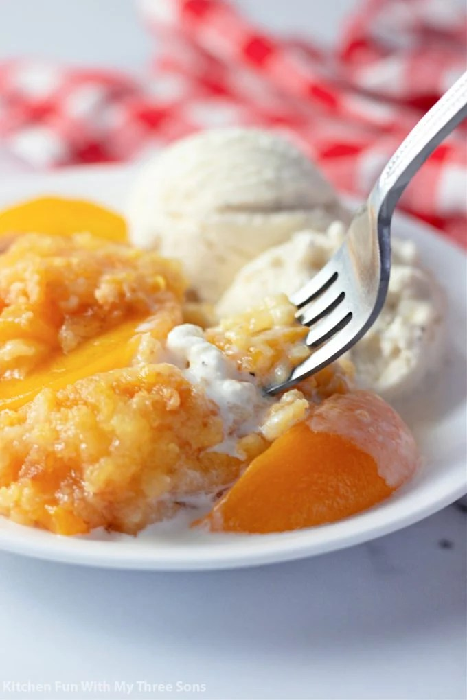 Easy Peach Dump Cake with a fork and vanilla ice cream.