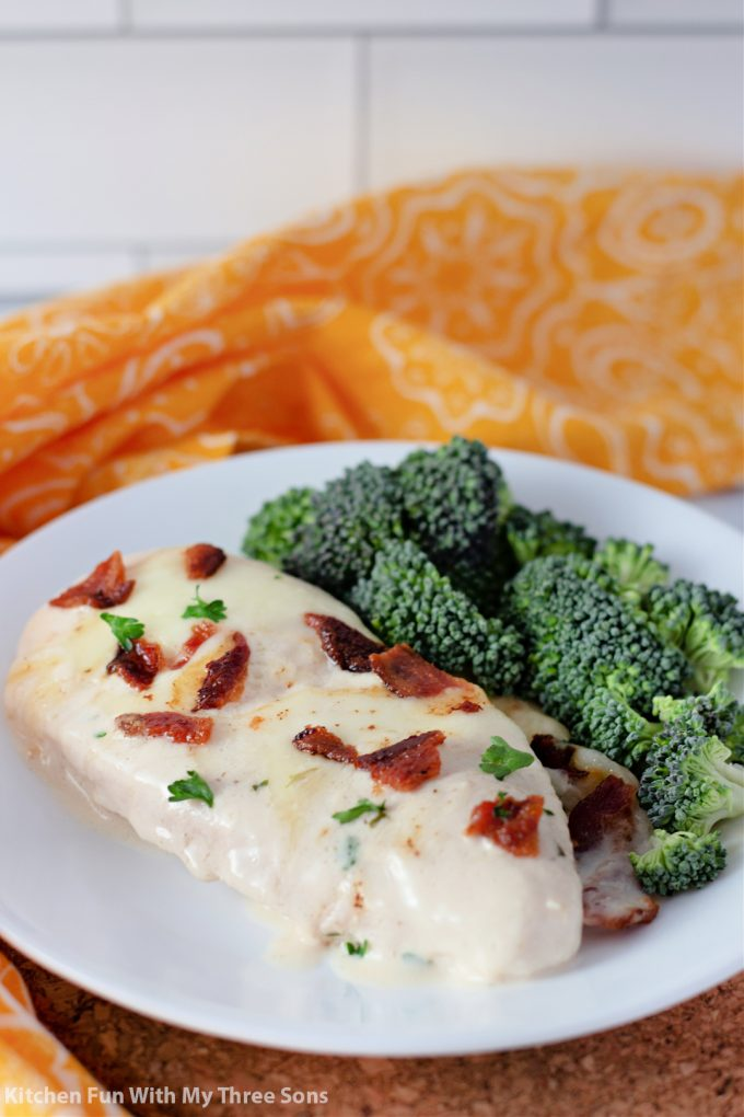 Cheesy Smothered Chicken with Bacon on a white plate with broccoli.