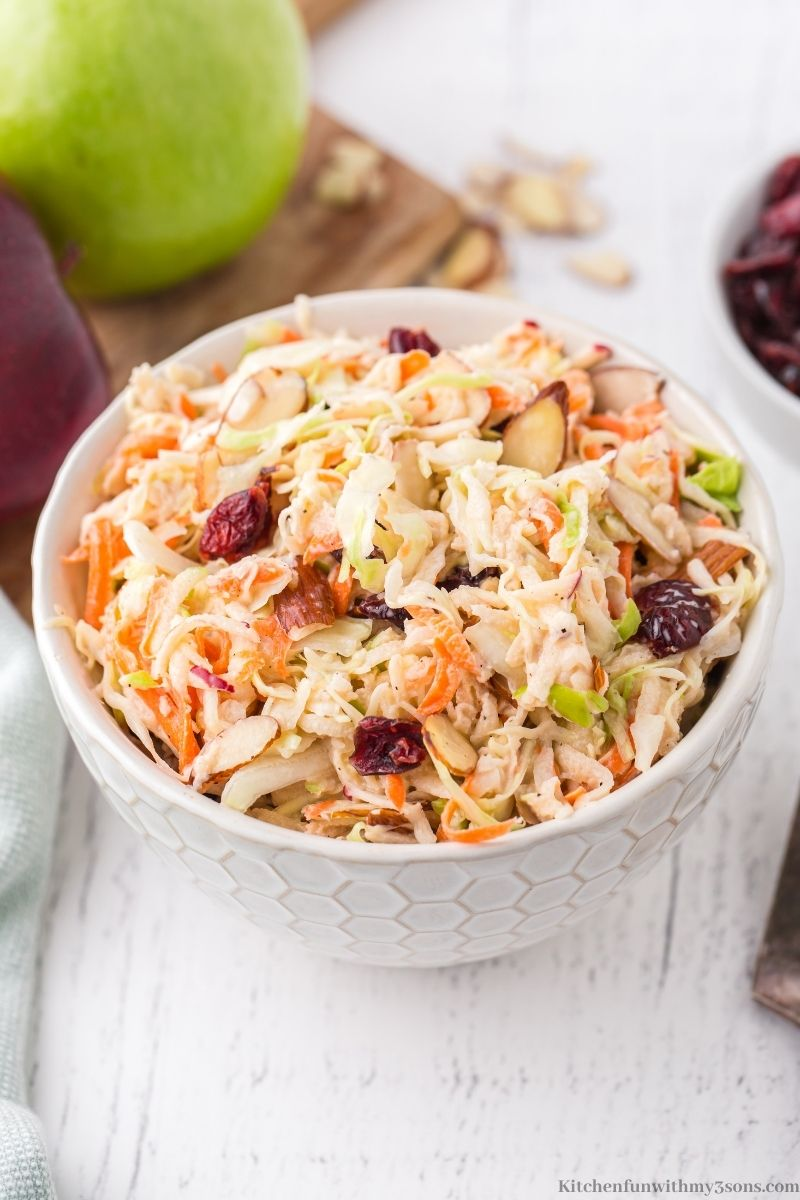 The Apple Slaw on a white wooden table with apples on a wooden board behind it.