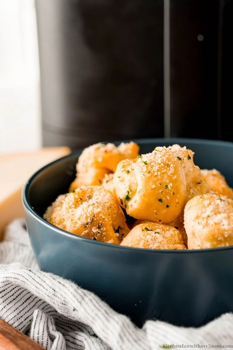 The finished garlic knots in a navy blue bowl.